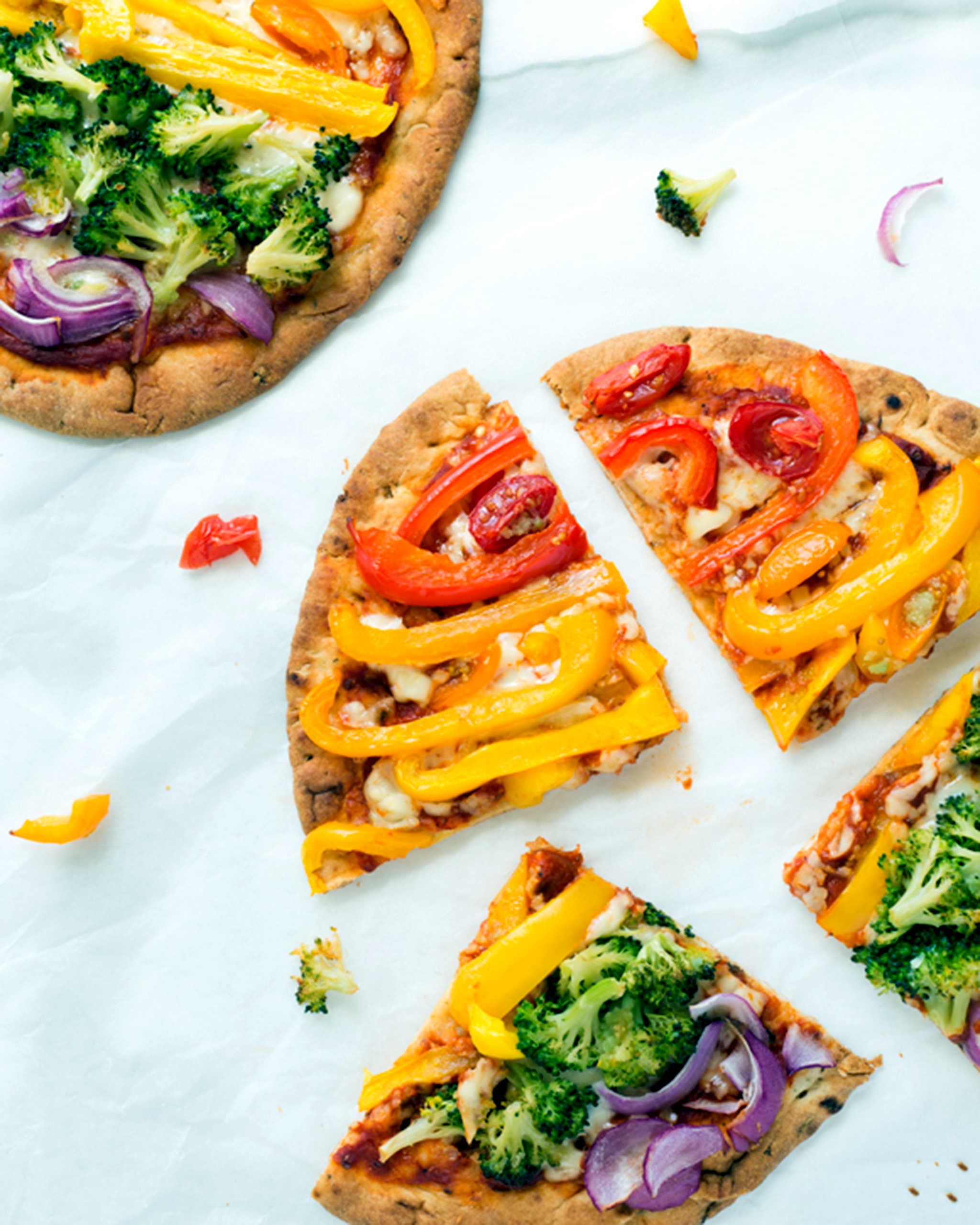 A photo of rainbow flatbread pizza topped with green and yellow peppers
