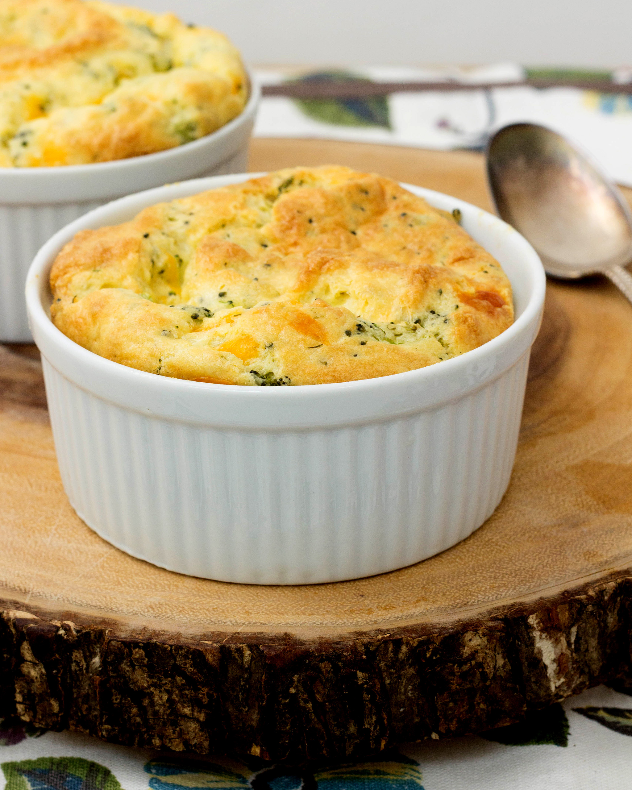 A photo of a finished broccoli soufflé in a white ramikin