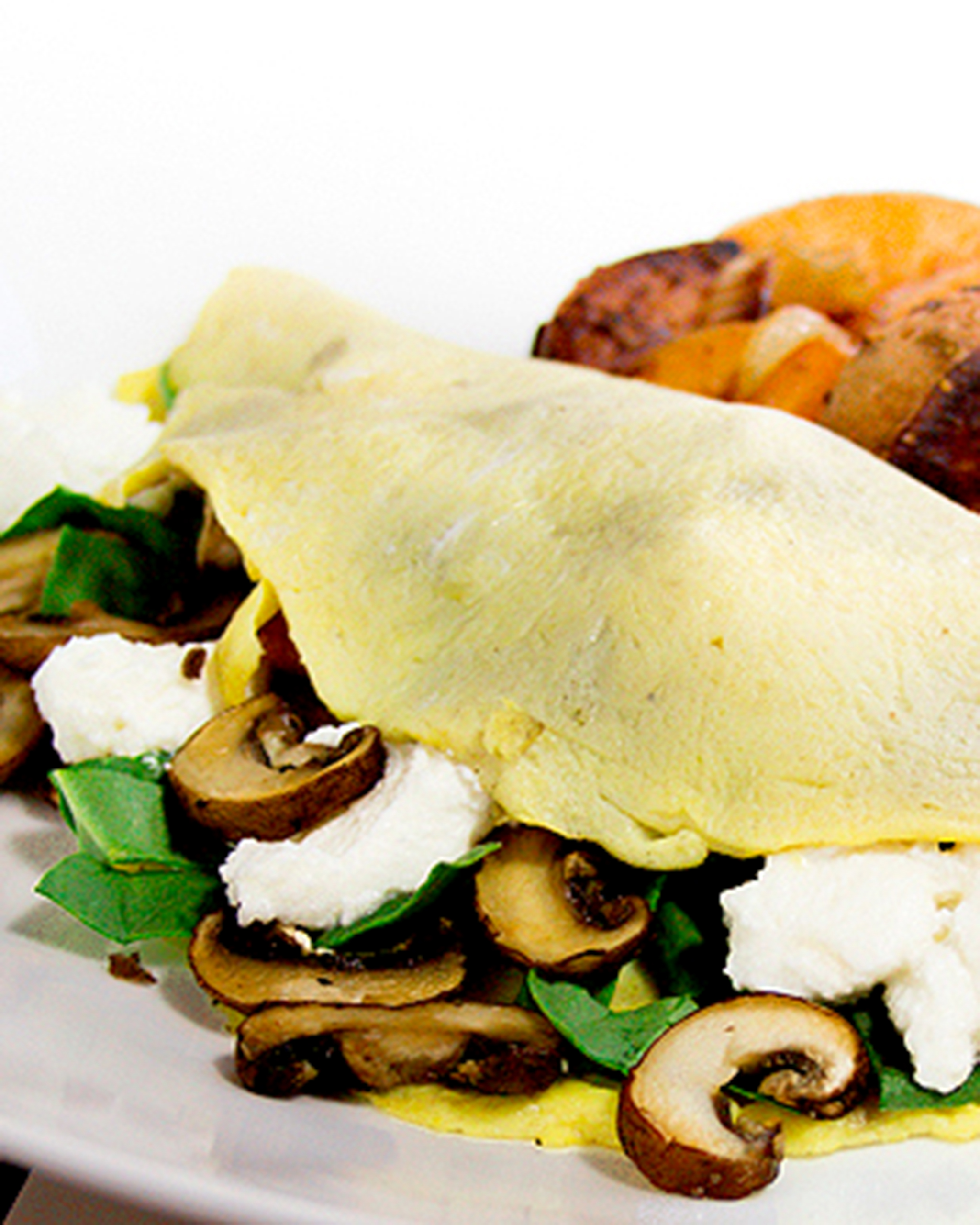 A close up of a mushroom, spinach, and ricotta omelette