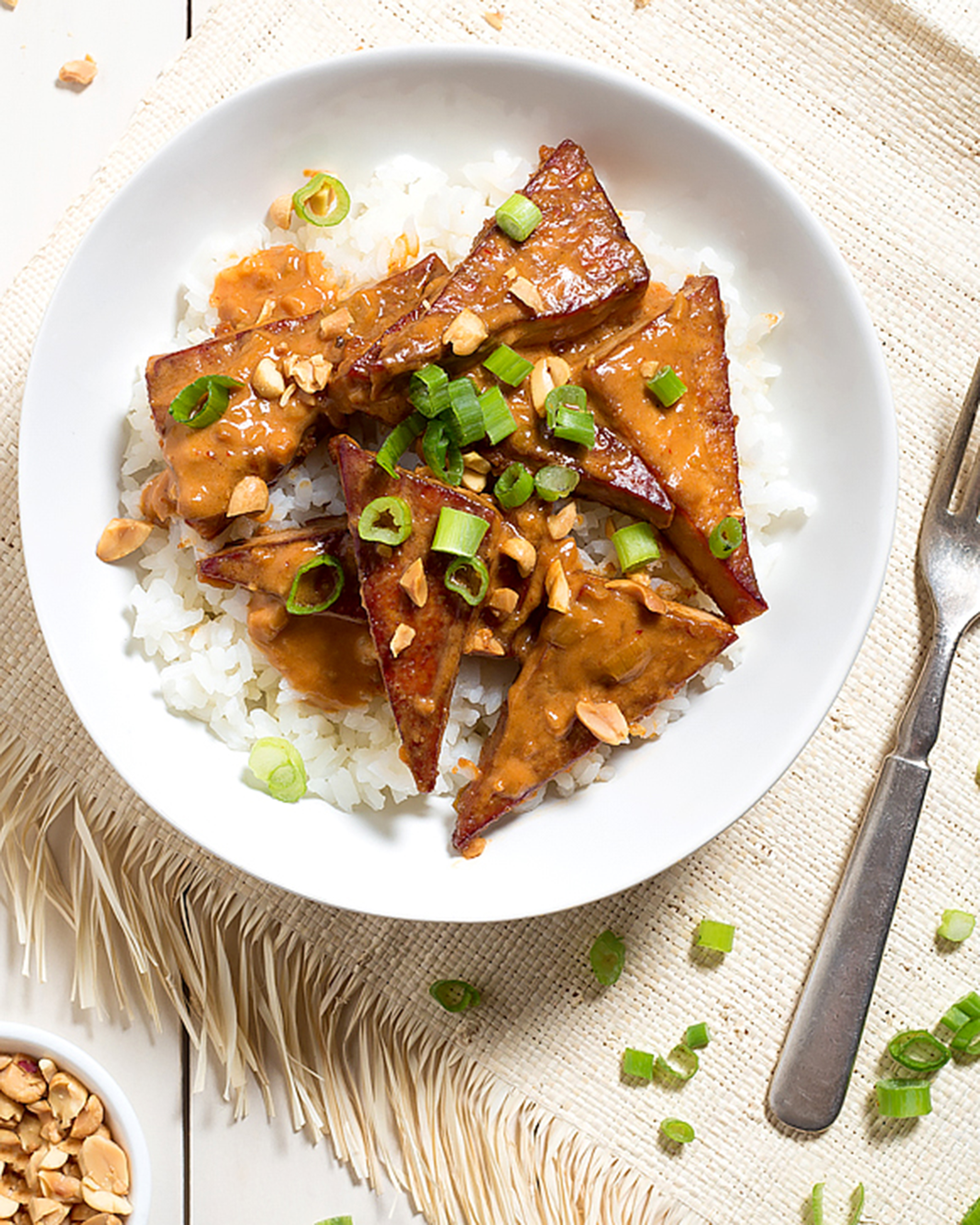 A photo of a spicy peanut butter tofu on top of white rice garnished with green onion.