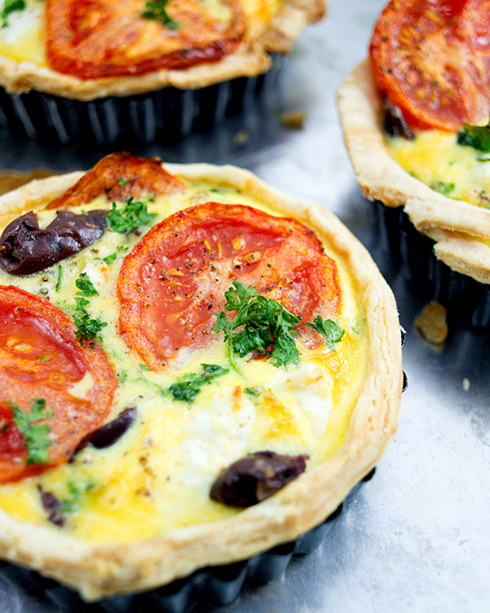 A photo of a serving of delicious fresh tomato and olive quiche.